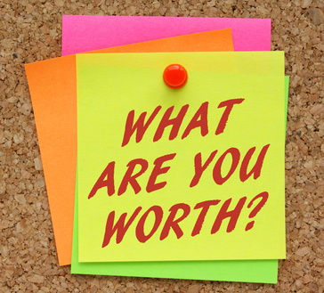 The question What Are You Worth in red text on a yellow sticky note as a reminder to assess your value in terms of financial rewards