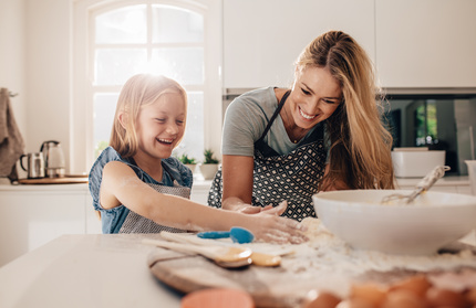 Happy young girl with her mother making dough. Mother and daughter baking in kitchen.