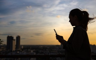 Silhouette of a woman use mobile phone in city background